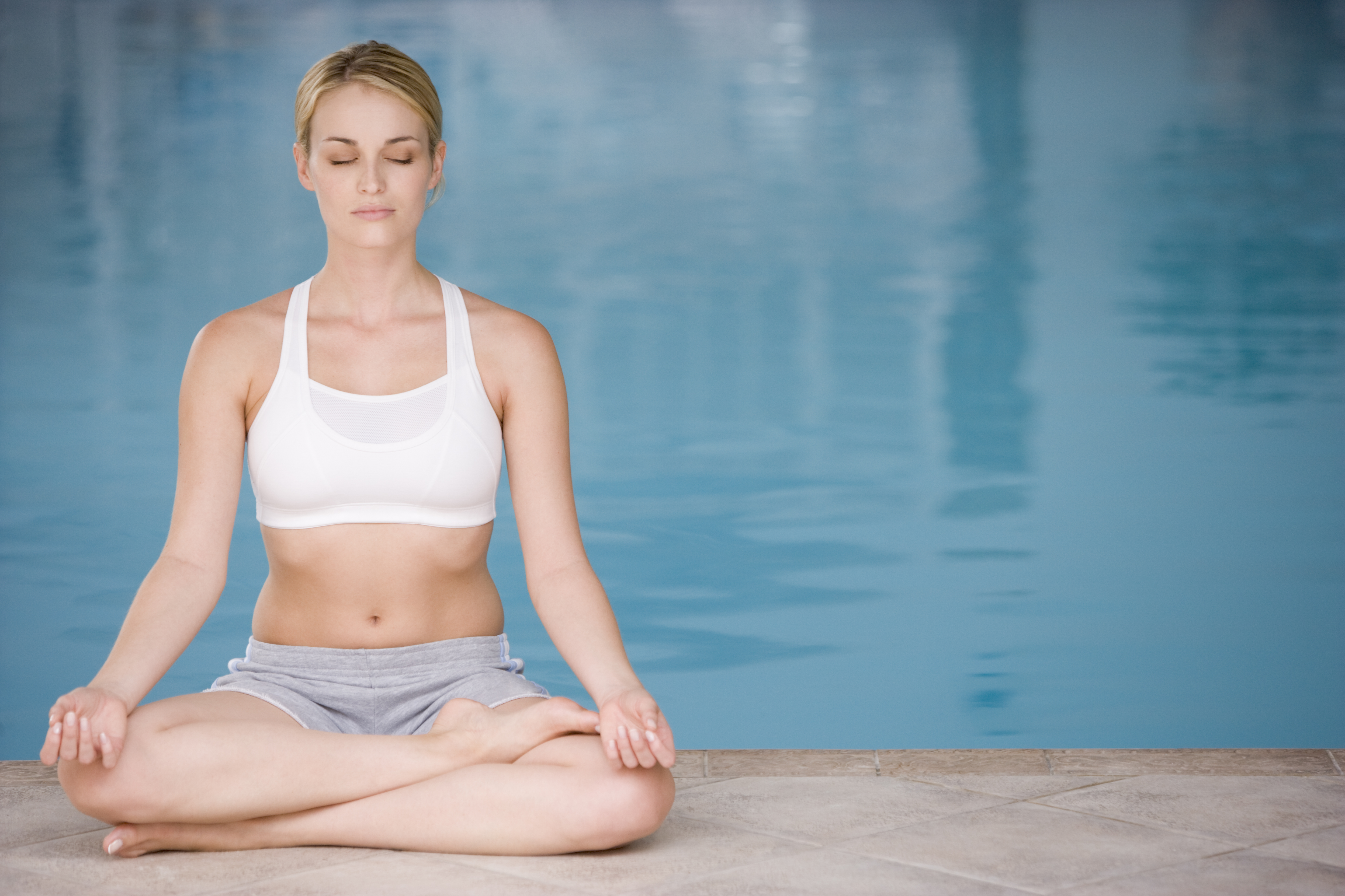 Woman sitting poolside doing yoga